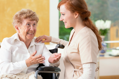 smiling elderly woman talking to a friendly caregiver