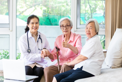 family nurse smiling with senior patient during home visit with visitor