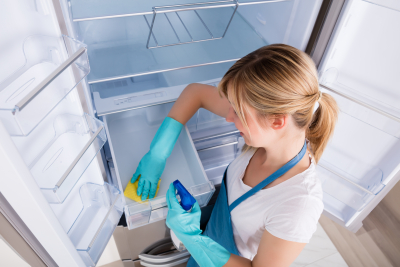 young woman cleaning empty refrigerator